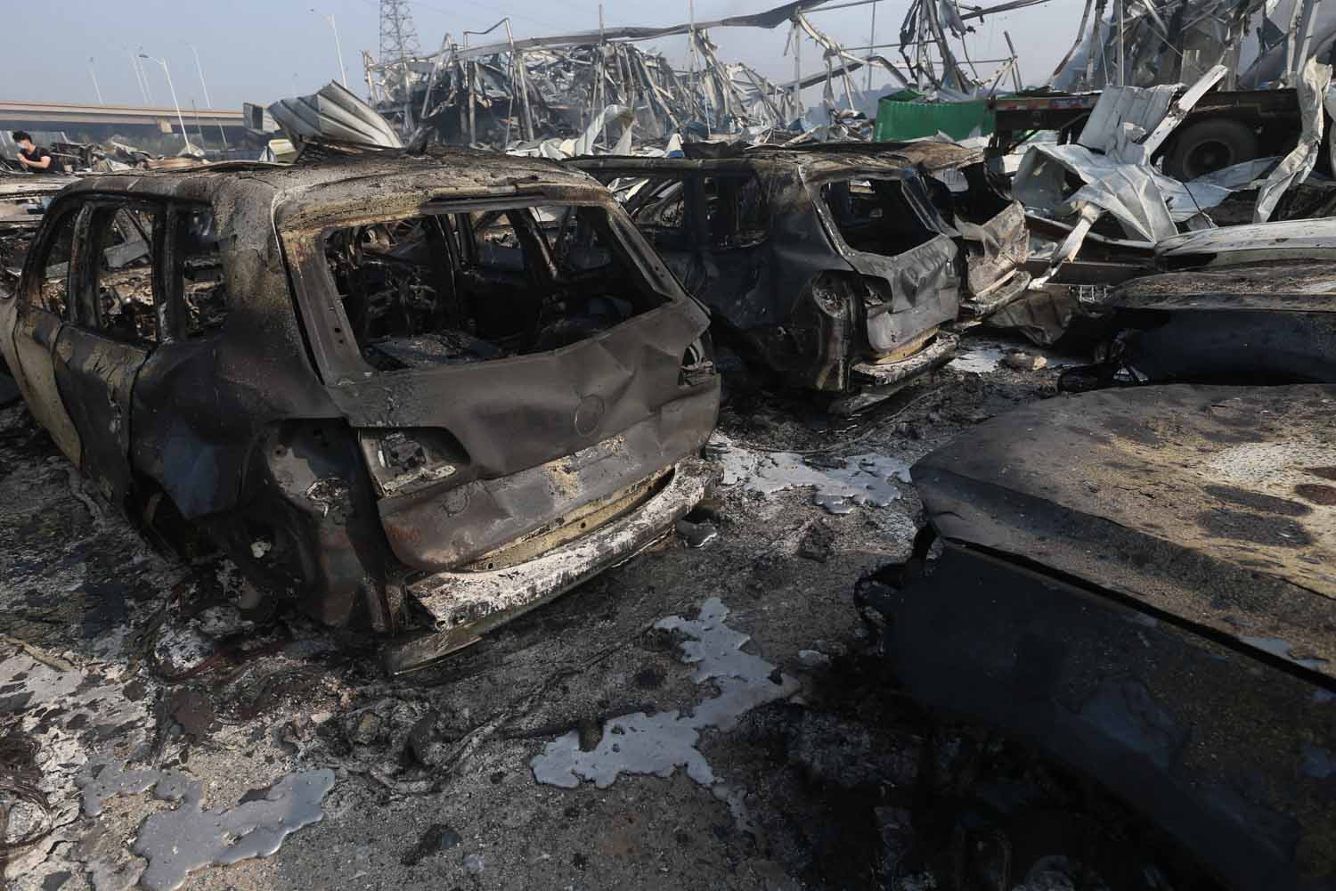 TIANJIN, CHINA - AUGUST 13: (CHINA OUT) Burnt cars are seen in the debris following the explosions of a warehouse in Binhai New Area on August 13, 2015 in Tianjin, China. At least 17 people dead, 32 are in critical condition and at least another 400 injured during the explosions of a warehouse on late Wednesday in Binhai New Area in Tianjin, according to police authority.  (Photo by ChinaFotoPress/ChinaFotoPress via Getty Images)