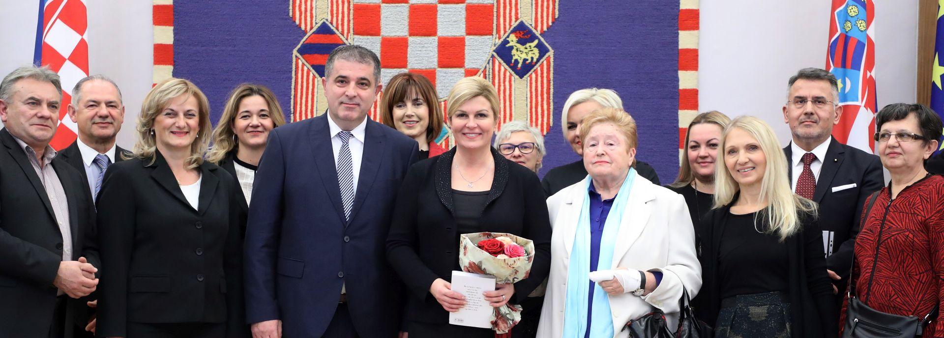 Predsjednica Grabar Kitarović s volonterima koji pomažu siromašnima i u pučkim kuhinjama